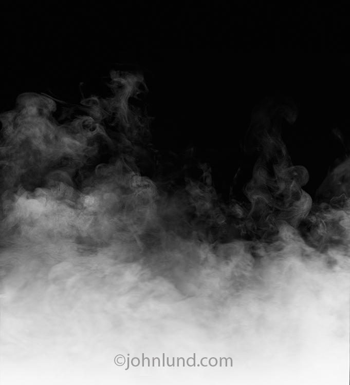 Steam rises against a black background in this stock photo that is perfect as a backdrop for type or for products shot associated withs steam, heat, mystery and cooking.