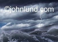 Stock photo of a raging storm in the ocean with a lightning strike in the distance. Violent waves, dark clouds, and lightning at night.