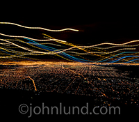 Big data streams over a city at night in the form of colored light trails in this stock photo about data collection, management, and distribution over communications technology,