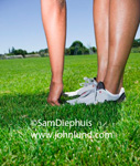 Photo of a pair of womens legs and one hand and arm. Woman is standing on the grass with one hand touching the grass. Stretching on the grass.  Knees down visible.