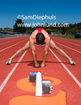 Picture of athlete on track. Athlete is a runner and is stretching before the event.  Starting blocks on track in front of runner.  Picture of track and field event.