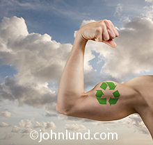 An arm with a flexed-bicep and a recycling symbol tattooed on it is held in front of an uplifting cloudscape is a concept image about environmental issues, sustainability, and ecological responsibility.