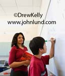 Picture of teacher and student during classroom activities.  A young male student is writing on the classroom whiteboard as the teacher watches. Teacher is an african american woman and the young elementary scool student is Asian.