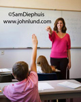 Picture of  teachers and students interacting in the classroom. A teacher wearing a bright pink sweater is pointing to a student who has his hand raised.  Middle school and grade school pictures of teachers and students.