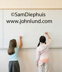 School room photo of two young female students at the front of the classroom drawing on the whiteboard. One young girl has pigtails and the other has shoulder length brown hair. They are drawing pictures of houses and stick figure people.