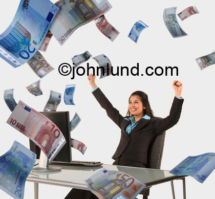 Different kinds of money flying out of a woman's computer monitor. The ethnic woman is  happy and has her fists held up over her head as a sign of success or victory. Money is filling the room.