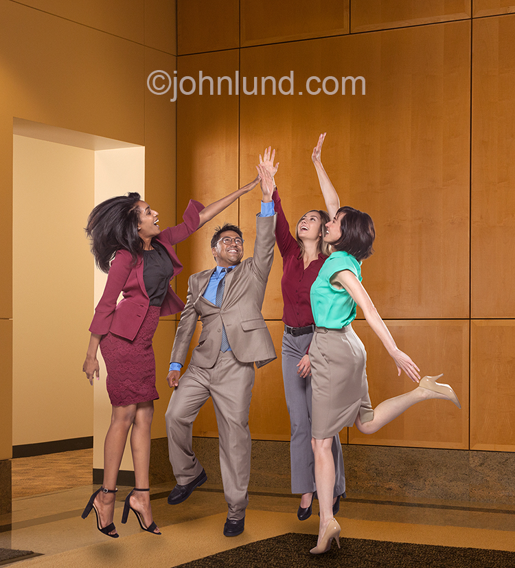 "Four business executives energetically engage in a ""high five"" celebration in a stock photo about success, teamwork, and achievement in the business world."