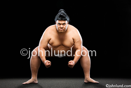 Stock photo of a crouching Sumo wrestler. He has  a serious mean look on his face. The image has a black background. Japanese sumo wrestler pix.