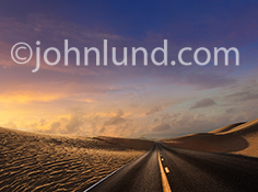 A deserted desert road stretches over distant sand dunes under a brilliant sunrise in a photo about journeys, possibilities, new beginnings, freedom and the way forward into the future.