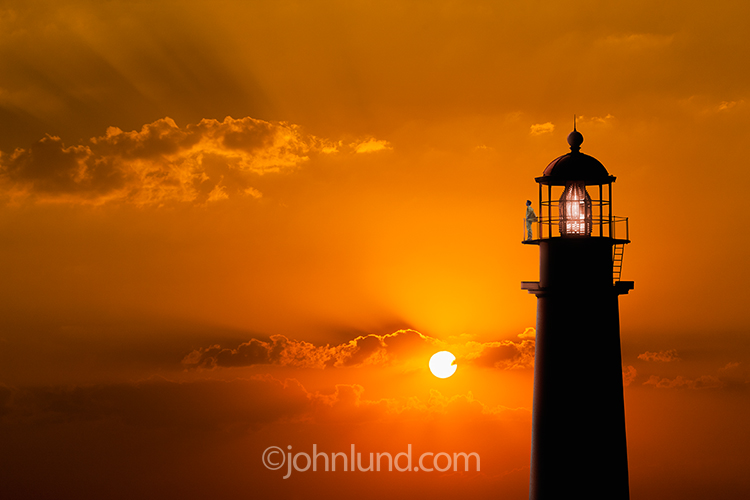 A lighthouse keeper stands atop a lighthouse scanning the horizon at sunset in a beautiful, tranquil image about guidance, security and safety.