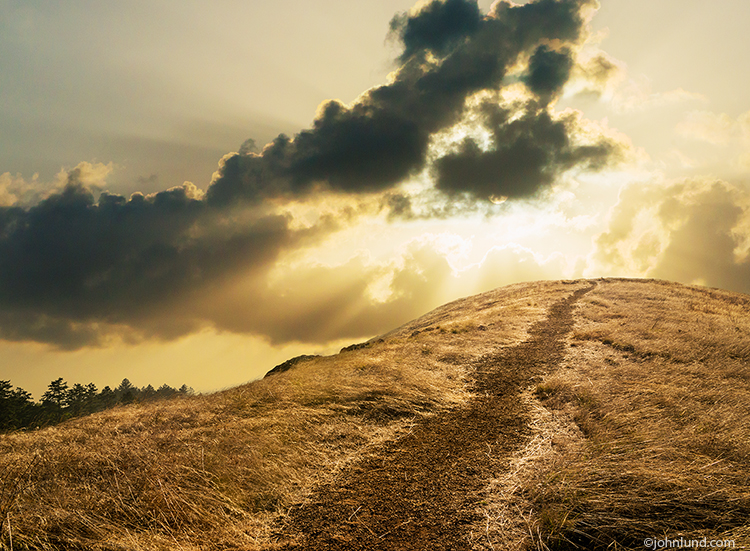 A path winds its way up a hill against a golden sun breaking out from behind dramatic skies in a concept image about spirituality, change and nature.