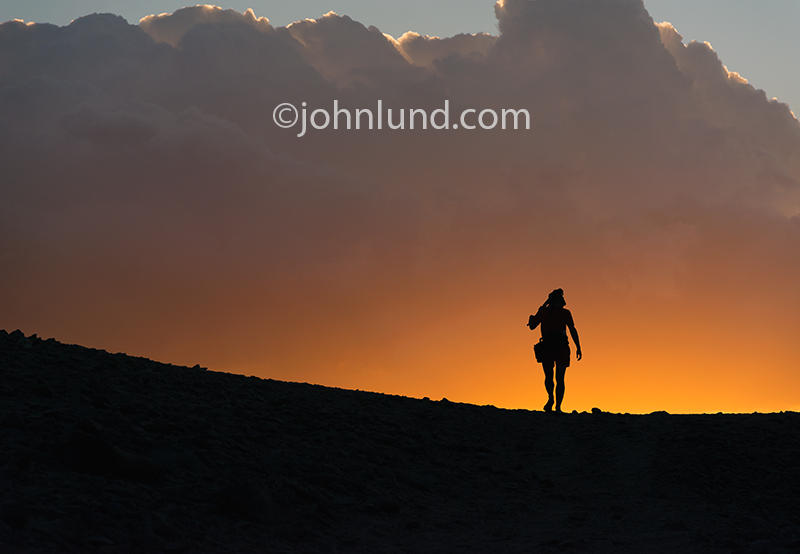 A photographer ascends a ridge on the island of Socotra at sunset.
