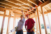 Picture of two males, one a superintendent and the other a carpenter. The super has a clipboard and is pointing. The carpenter is wearing a tool belt and is listening the supervisor. Stock pics for ads.