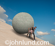A couple, consisting of a woman and a man, are pushing a gigantic ball of money up a steep concrete incline in this image about investment challenges, money issues facing couples, and financial planning for the future.