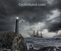 A tall ship cuts through an ocean storm and past a lighthouse standing resolute against a sky filled with ominous and dark storm clouds in a stock photo about guidance and safety as well as challenge and risk.