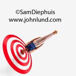 Strange and bizarre image of a male gymnast with his head stuck in a bulls eye target as though he was an arrow that had been fired from a bow. Target practice for gymnasts.