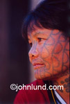 Adventure and travel stock photo of a tattooed Hmong Tribal Woman. Some Burmese tribes began the practice of tattooing the faces of the women to prevent the King from taking them for his wives.