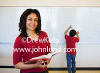 Pictures of teachers and students for advertising.  This hot ethnic school teacher is smiling at the camera and holding a school text book open in her hands.  She has shoulder length black hair. In the background a young boy is writing on the chalkboard.