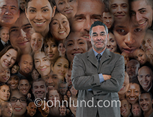 A businessman of Asian descent stands in front of a montage of people's portraits in a powerful image about leadership, support, resources and even social media and networking.