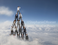 Picture of a pyramid of business men and women standing on each other's shoulders illustrating the concept of teamwork and vision as it rises high above the clouds.