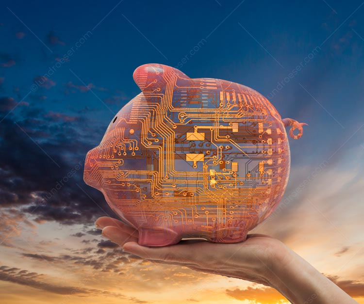 This tech piggy bank stock photo features a hand holding up a computer circuitry piggy bank against a brilliant sunrise.