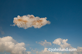 Pictures of Cloud computing technology is portrayed in this photo by computer circuitry visible within a cloud floating against a blue summer sky.