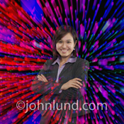 A young Asian woman executive photographed against a high tech background of streaking colored lights.