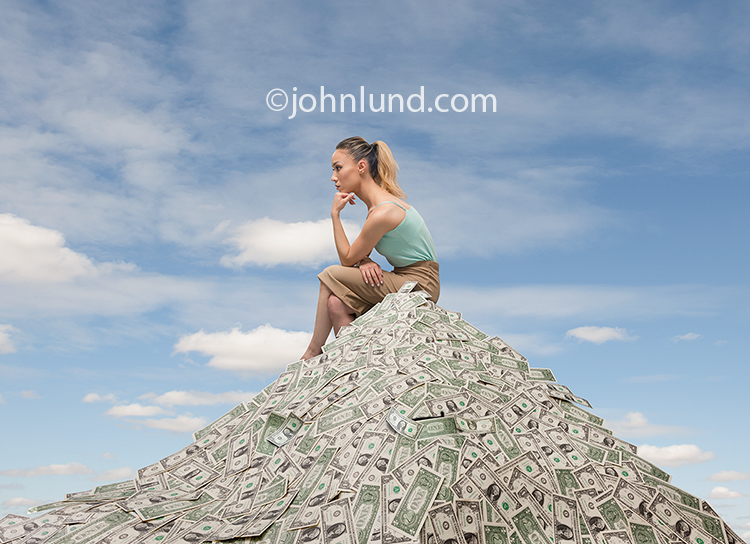 "A woman, in ""the thinker"" pose, sits atop a huge pile of dollars and thinks about money, finance and investment in a stock photo about money, finance and investment planning issues."