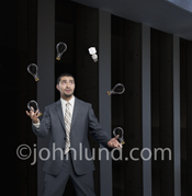 An Hispanic businessman juggles six light bulbs one of which is an environmentally friendly CFL bulb as he thinks up new green ideas.
