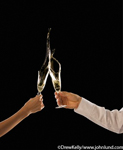 Picture of a toast being made. Black background with a woman's arm and a man's arm in a white sleeve and the hands are holding champagne glasses being clinked. Clinking champagne glasses.