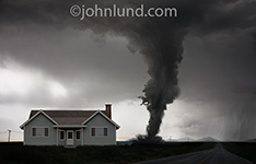In this photo a huge tornado closes in on a home threatening it with total destruction in an image about risk, danger and the power of nature.