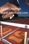 Picture of female strack star running the high hurdles. She is in the air clearing a hurdle. Legs and torso only.  High hurdles pic.