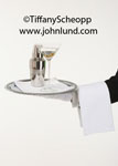 Stock photo of a butler's hand holding out a sliver serving tray with a martini and a martini shaker.  The butler has on a white glove and has a white towel draped over his arm. The martini has two olives in it. Ad pics of butlers serving drinks.
