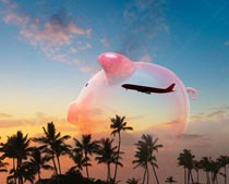 A piggy bank is superimposed over palm trees and a commercial jet in a stock photo about saving for travel and vacation trips.