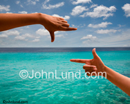 Picture of hands framing a tropical ocean. The water is clear and blue and the sky is blue with patchy clouds. Great for Tropical Retreat and Luxury Spa Advertising Photos.