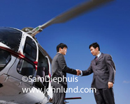 Two Asian businessmen shaking hands while standing under the rotating blades of a helicopter. Asian Businessman VIP pix.
