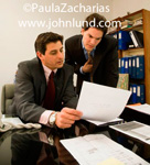 Executives going over some paperwork together. One man is seated the other standing, bending down to get a closer look at the legal documents the hispanic executive is holding. Hispanic business stock photo for advertising.