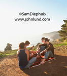 Picture of  group of young friends sitting on a spread out picnic blanket on a dirt path overlooking the coast. One guy is barefoot and another guy is playing a guitar. Friends on an outing to the coast.