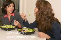 Picture of women eating salads for lunch. Two office workers or businesswomen are chatting and eating salads from bowls.  Photos of eating healthy in the workplace. Food pictures for advertising.
