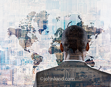 A businessman looks off towards a global map multiple exposed with numerous cityscapes in a stock photo about a confusing and uncertain future.