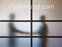 This unusual handshake picture of successful negotiation and agreement reveals two business people shaking hands behind a frosted glass office partition.