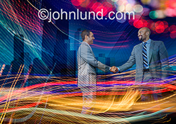 Urban business connection is just one of the concepts illustrated by this colorful and dynamic business stock photo of two executives shaking hands while engulfed in streaks of colored lights and against a background of high rise buildings.