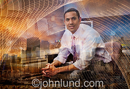 Urban business technology is indicated in this rich and complex stock photo of a businessman surrounded by a rich tapestry of buildings and light patterns indicating technology, networks and connections.