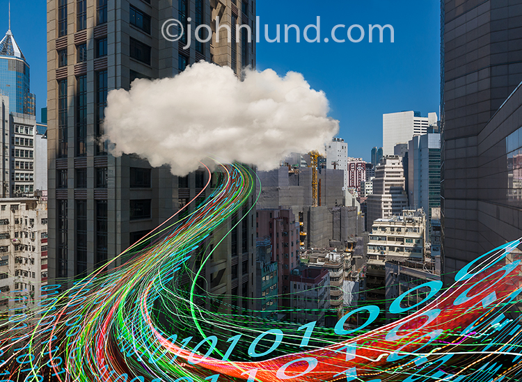 Urban cloud computing, networking and connections are cleverly shown in this stock photo of a cloud amid high rise office buildings with streaming data in the form of binary numbers and colored light trails flowing out between the buildings.