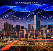 A futuristic looking city is inundated in lines of colored lights representing communications technology and streaming data.