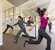 Five business people race through an office on urgent business in this humorous stock photo.
