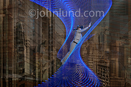 Virtual reality in business is the primary concept in this stock photo featuring a woman in business attire, wearing VR headgear, flying up a vortex of blue light trails against an abstract metropolis background.