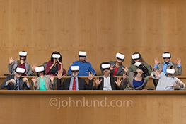 Twelve jurors react to what they see in their Virtual Reality headgear while in a courtroom jury box in a stock photo about technology in our legal system.