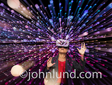 A woman takes a dramatic virtual reality trip in a stock photo showing her wearing VR headgear and surrounded by speeding streaks of light.