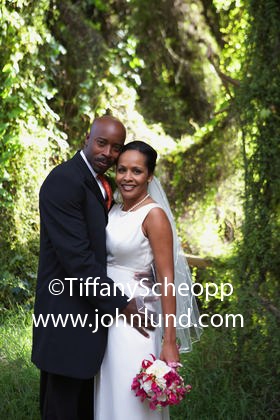 A bride and groom of African heritage are hugging each other as they pose for the wedding photographer and wait for the picture to be snapped. The scenic backdrop is a vine covered forest with spots of sunlight breaking through here and there.
